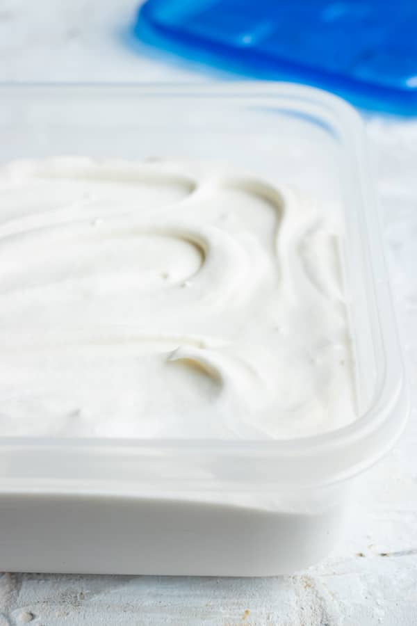A plastic storage container showing how long homemade coconut cream lasts.