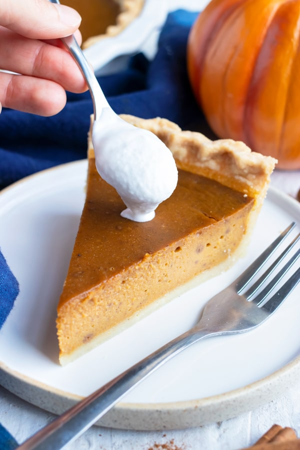 Vegan whipped cream being placed on a piece of dairy-free pumpkin pie.