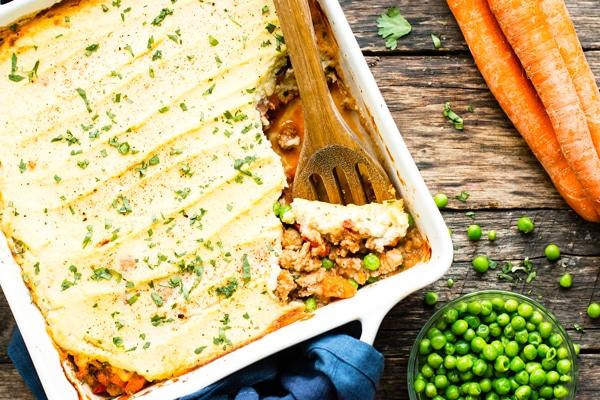 Gluten-free turkey shepherd's pie in a casserole dish with a wooden spoon to serve.