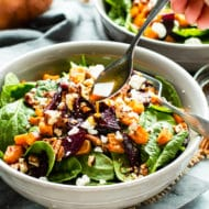 Roasted Beet Salad with Goat Cheese & Sweet Potatoes is a show stopper! Spinach leaves are coated in a sweet and tangy balsamic vinaigrette and then topped with hearty root vegetables for an anti-oxidant rich gluten-free, and vegetarian Thanksgiving salad recipe.