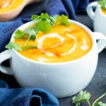 A serving bowl full of healthy, Paleo, Whole and vegan roasted butternut squash soup with a drizzle of coconut milk and a cilantro sprig on top.