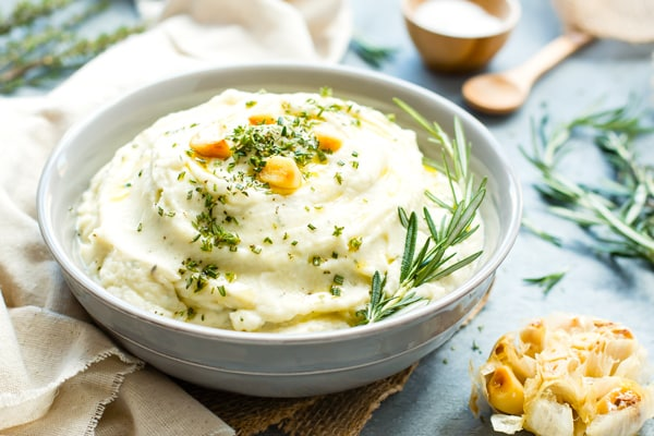 Garlic mashed cauliflower recipe with roasted garlic, rosemary and thyme in a grey bowl with a tan napkin.