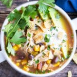 Crock-Pot chicken tortilla soup with fresh cilantro, sliced avocados, and sour cream on top.