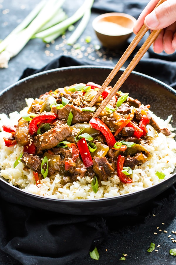 Gluten-free Slow Cooker Beef Teriyaki in a black bowl with chopsticks in one hand.