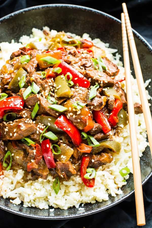 Gluten-free Beef Teriyaki in a bowl on top of rice with chopsticks.