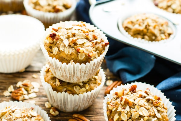 Two Vegan Maple Pecan Oatmeal Muffins on top of one another on a table.