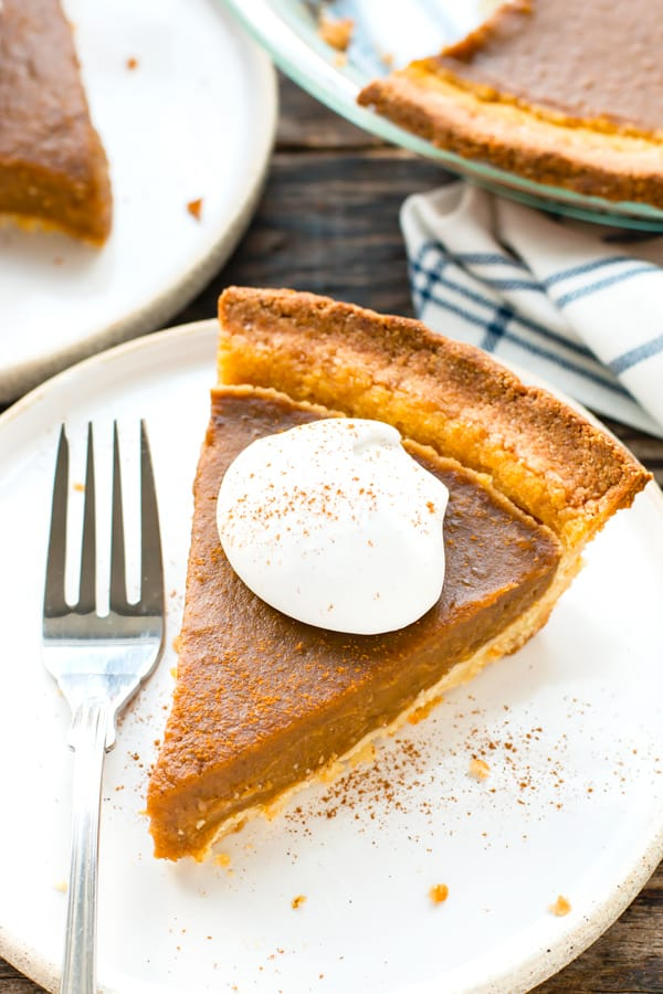 A piece of easy pumpkin pie on a plate with a fork for Thanksgiving dinner.