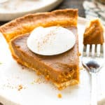 A single piece of gluten-free pumpkin pie with whipped cream on the top for dessert.