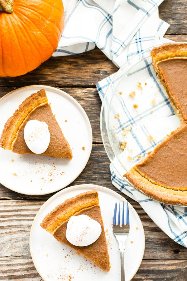 Two pieces of paleo pumpkin pie on white plates with a pumpkin on the side.