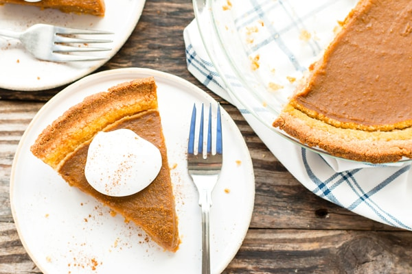 A piece of vegan pumpkin pie on a white plate for the holidays.