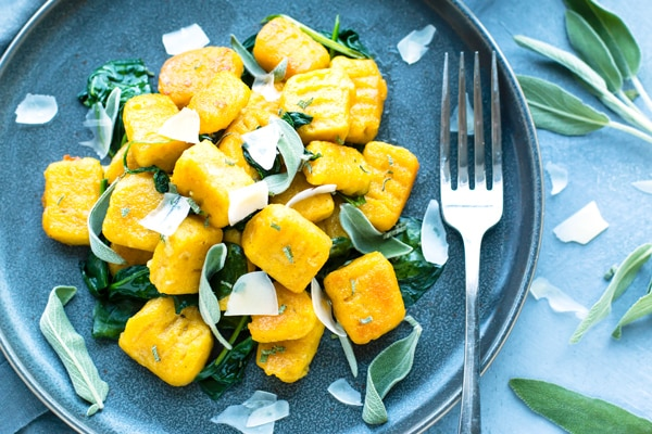 An overhead picture of gluten-free Butternut Squash Gnocchi with fresh herbs as a garnish.