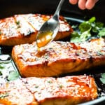 Honey sriracha sauce being drizzled on a salmon fillet in a black pan.