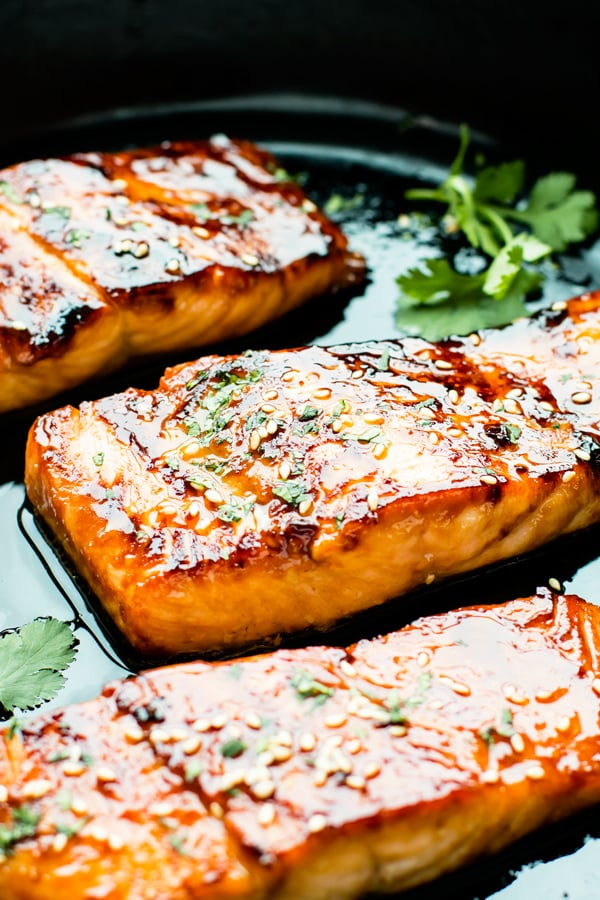 Three honey glazed salmon fillets in a black pan with fresh herbs.