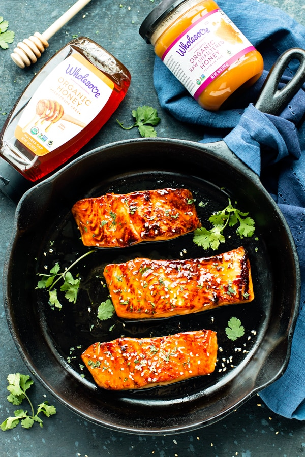 Gluten-free Honey Sriracha Glazed Salmon in a black cast iron pan with two bottles of Wholesome honey and sauce.