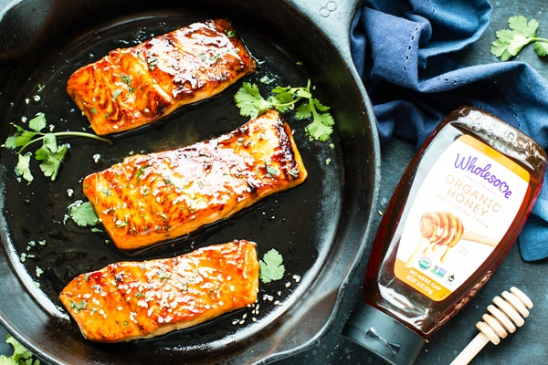 Three gluten-free Honey Glazed Salmon fillets in a black pan with a bottle of Wholesome honey on the side.