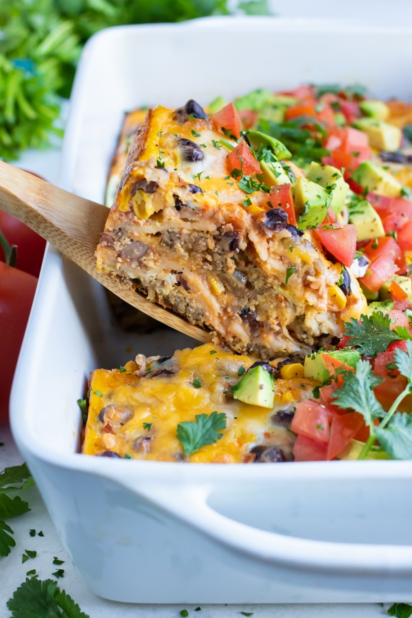 Mexican breakfast casserole is served with a wooden spoon.