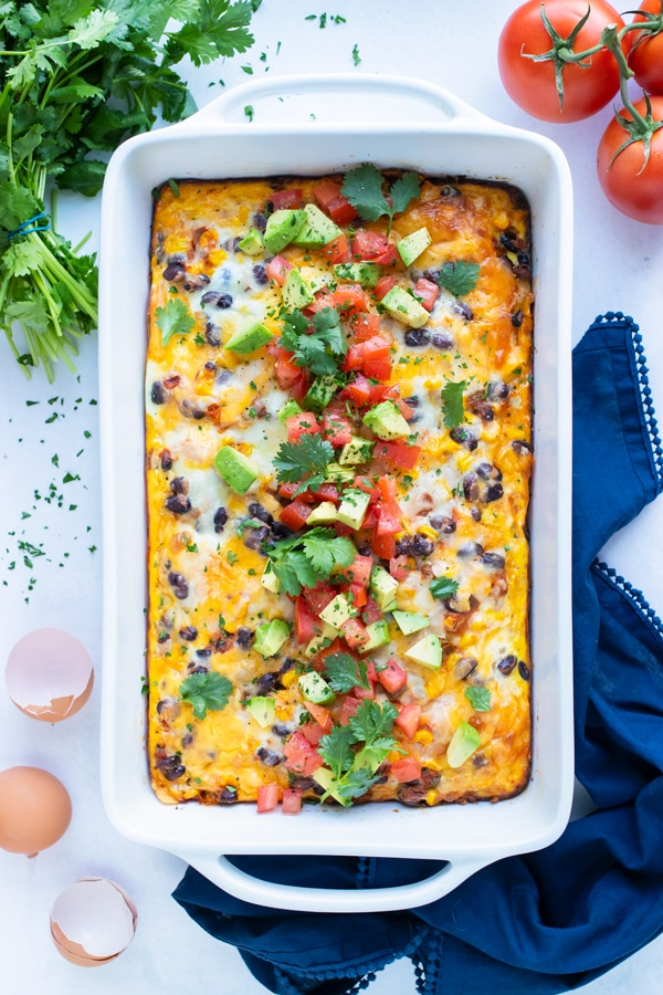 Mexican Breakfast Casserole is served from a white casserole dish on the counter.