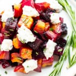 An overhead picture of gluten-free Oven-Roasted Beets on a white plate with fresh herbs.