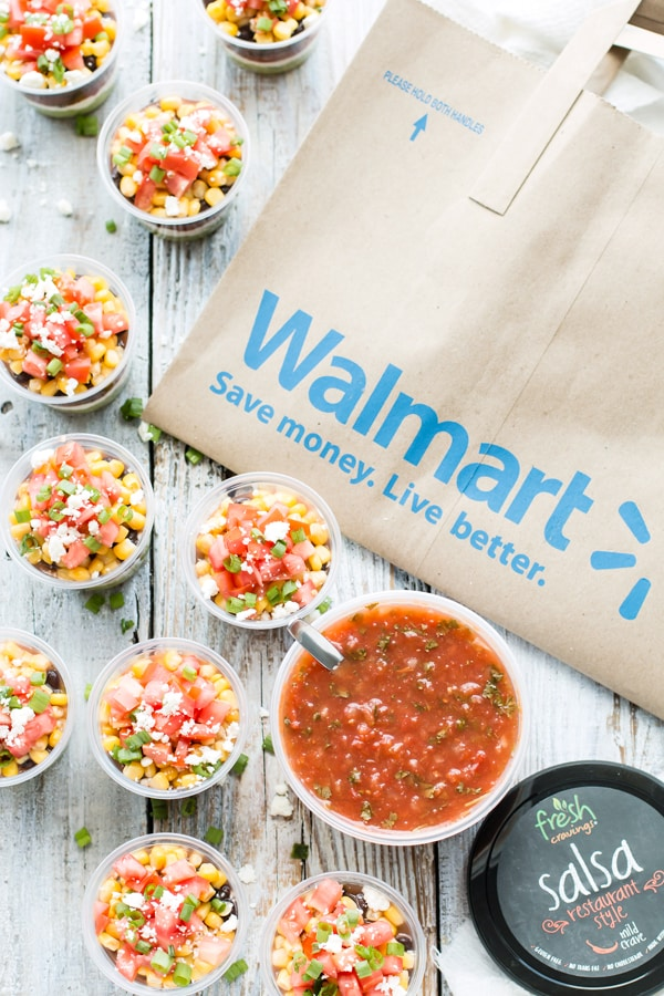 A picture of a Walmart bag on a table surrounded by cups of Healthy 7-Layer Dips and a container of salsa.
