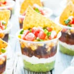 Plastic cups filled with gluten-free 7 layer dip recipes for a party or get together.