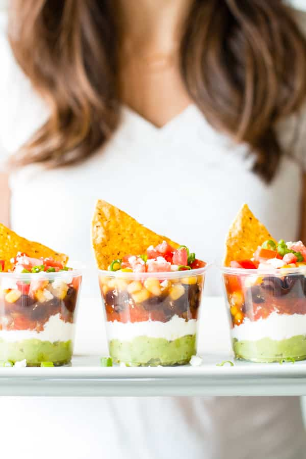 A woman holding a tray of gluten-free 7 layer dip cups for a healthy lunch.