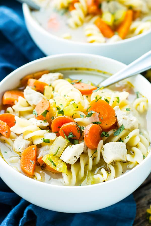 A bowl filled with gluten-free chicken soup with a spoon inside.