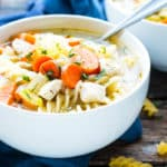 A white bowl filled with easy chicken and noodles as a soup for a healthy lunch.