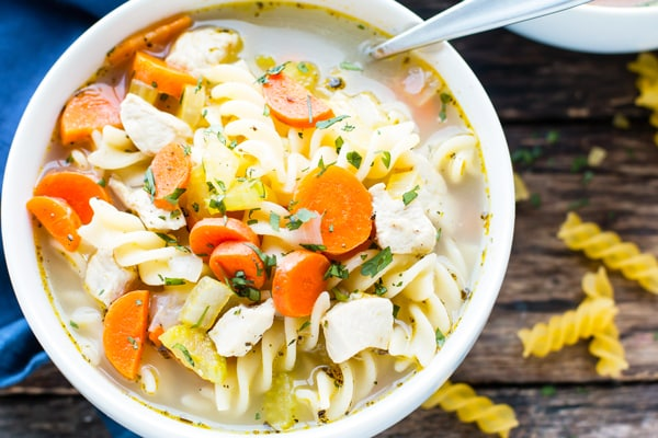 An overhead picture of gluten-free soup made with chicken, noodles, and vegetables.