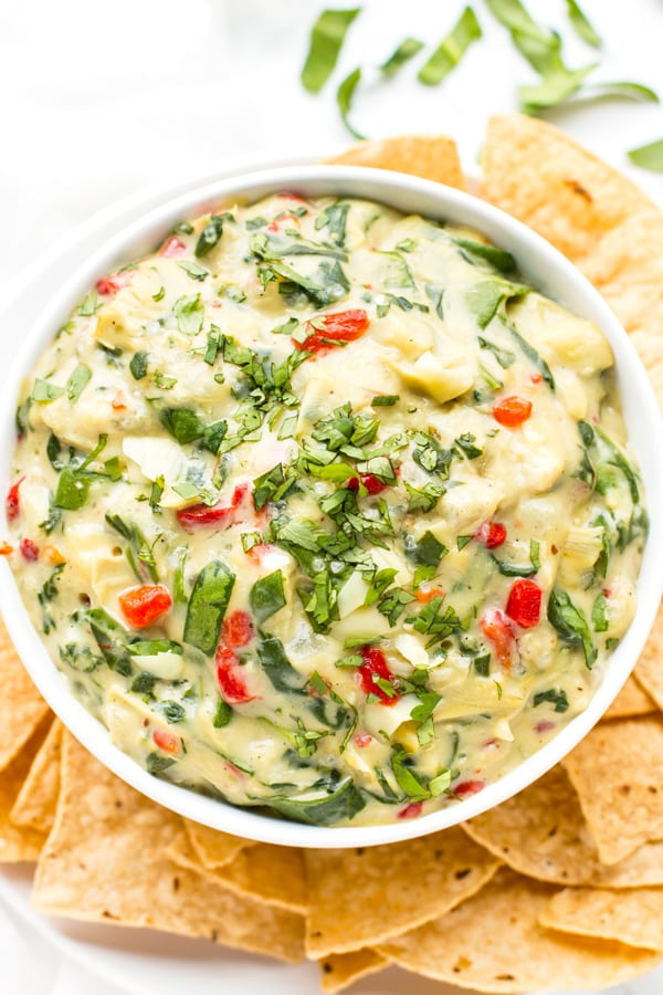 A gluten-free spinach dip recipe made with artichokes in a bowl with tortilla chips for dipping.