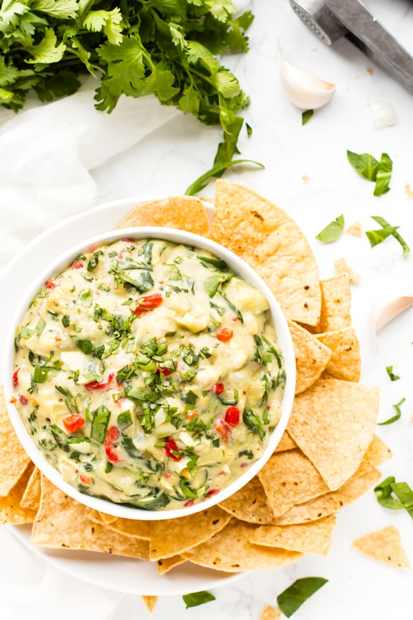 Gluten-free spinach artichoke dip in a bowl with tortilla chips for a healthy appetizer.