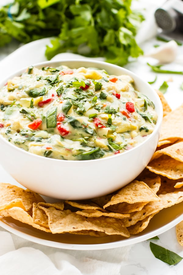 Healthy spinach artichoke dip in a bowl with tortilla chips for lunch.