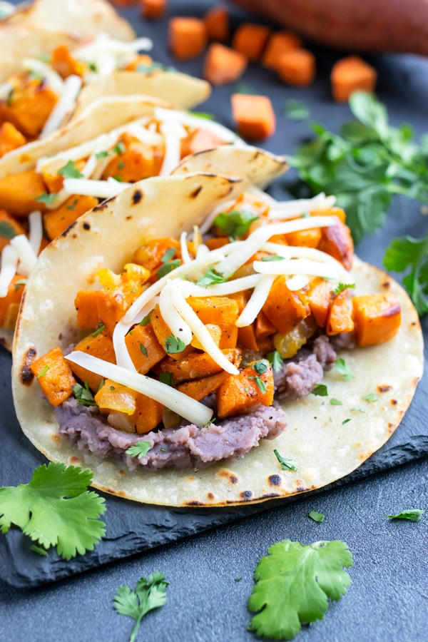 Vegetarian black bean sweet potato tacos with cheese in a corn tortilla.