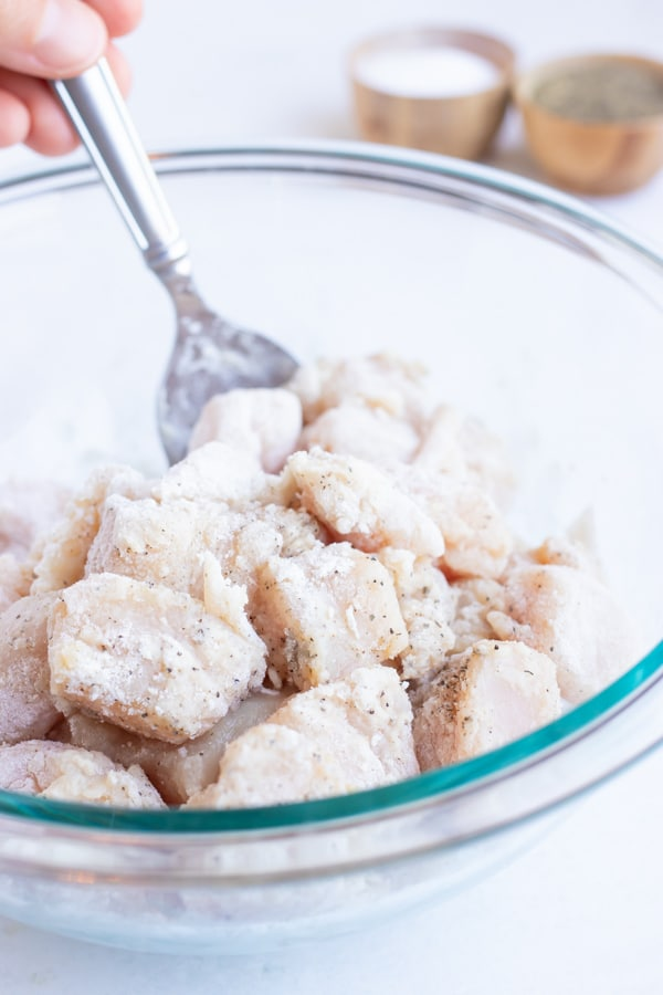 Chicken cubes being tossed in a flour mixture.