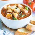 A soup bowl full of creamy roasted tomato basil soup with homemade croutons.