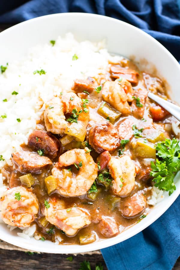 A bowl full of shrimp and sausage gumbo with a sprig of parsley.
