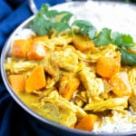 A close view of shredded chicken breasts in a yellow curry sauce with big chunks of sweet potatoes.