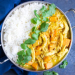An easy chicken curry recipe with a yellow curry sauce that was made in the slow cooker and served with white rice and cilantro.