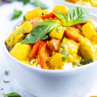 A white bowl full of a yellow curry recipe.