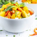 A white serving bowl of Thai curry that is made with yellow curry paste, chicken, potatoes, and carrots.