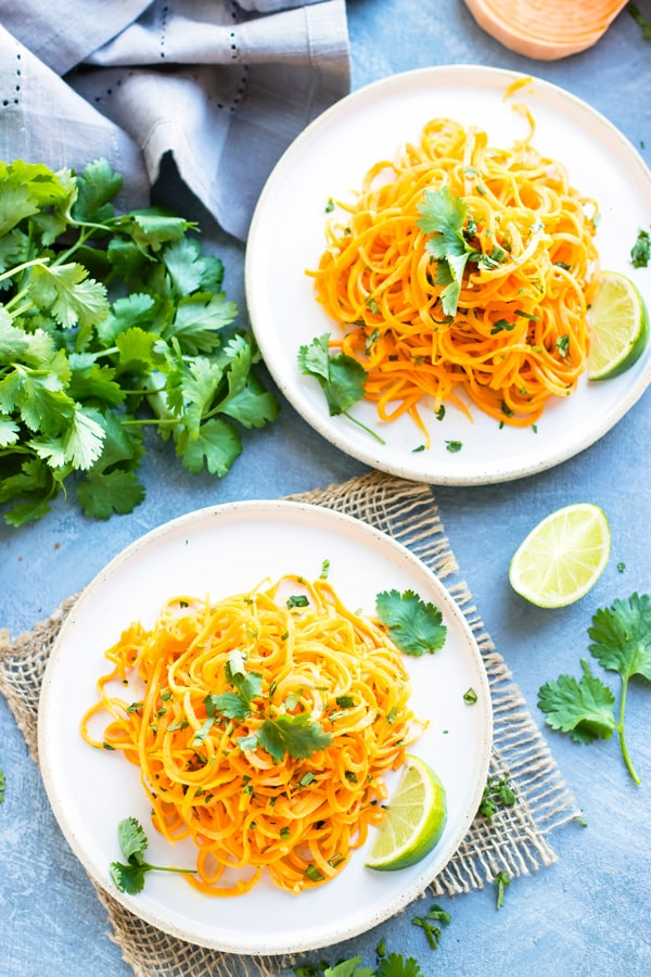 Two white plates filled with Cilantro Lime Sweet Potato Noodles with fresh cilantro on the side.