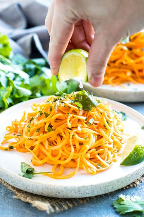 A hand squeezing the juice of a lime onto Cilantro Lime Sweet Potato Noodles.