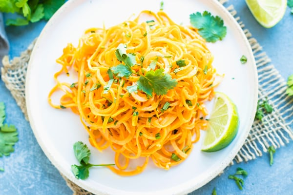 Gluten-free sweet potato noodles on a white plate with a lime on the side.