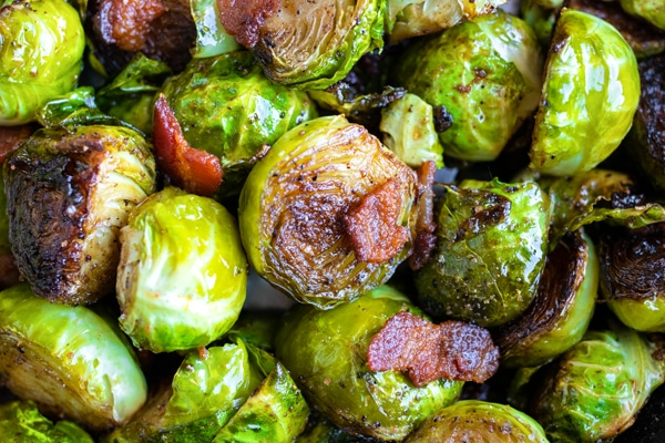 A close-up of a Brussels sprout with a piece of bacon that has been oven-roasted until crispy and caramelized.