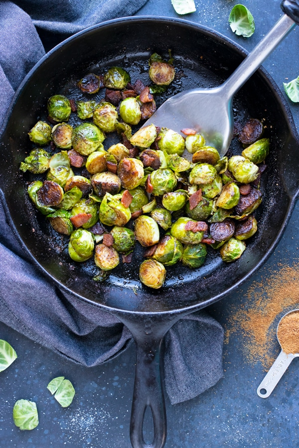 A cast iron skillet with crispy Brussels sprouts, Paleo bacon, and coconut sugar that have been roasted in the oven.