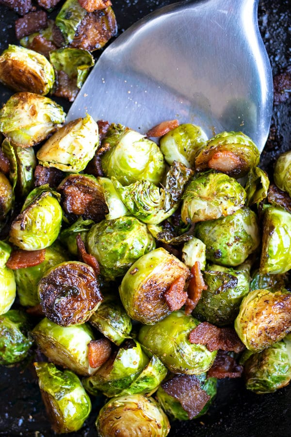 A cast iron skillet full of crispy and caramelized Brussels sprouts