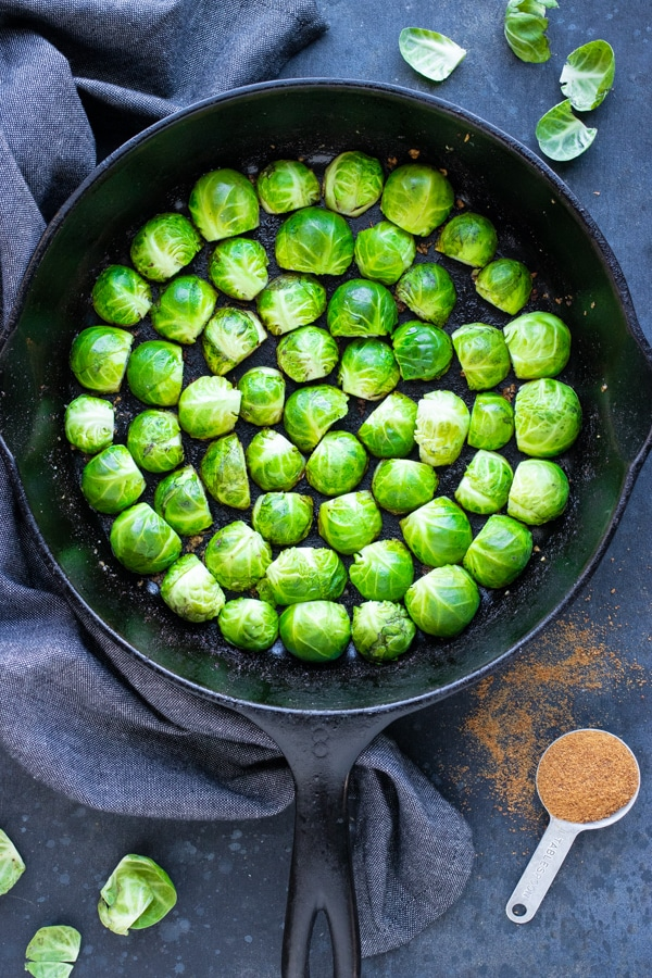 A cast iron skillet full of Brussels sprouts that do not overlap and are placed in a circle for a low-carb side dish.
