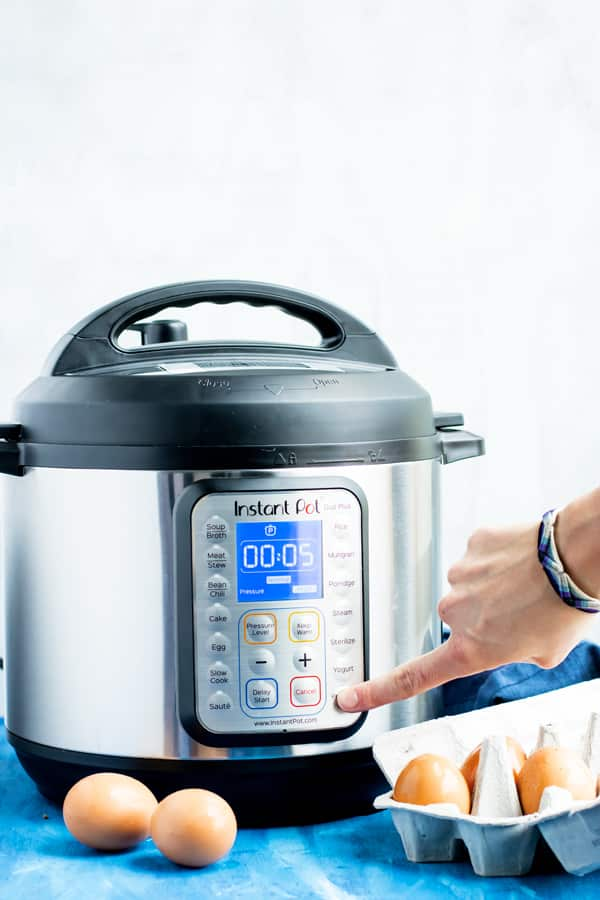 A hand pressing a button on an Instant Pot to make a hard-boiled egg recipe.