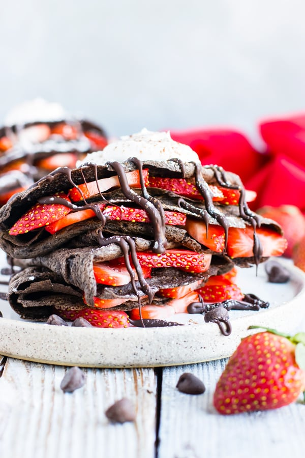 Paleo Chocolate Crepes with sliced strawberries on a plate for breakfast.