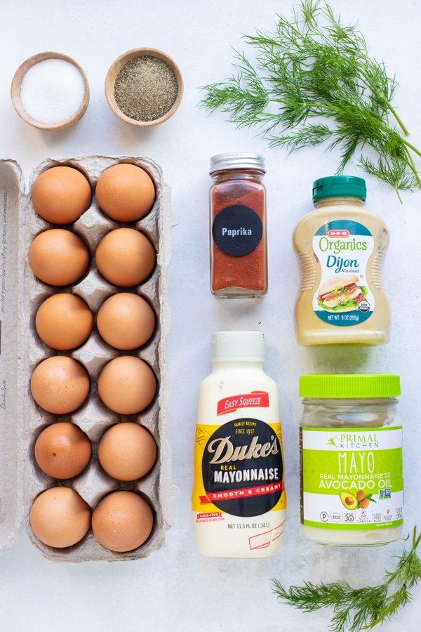 A dozen eggs, paprika, mayonnaise, mustard, dill, salt, and pepper as the ingredients for a classic deviled eggs recipe.