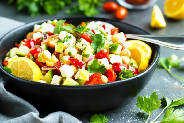 Gluten-free Mediterranean cucumber salad in a black bowl for an easy lunch.